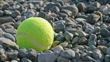 Tennis ball on a pebble beach