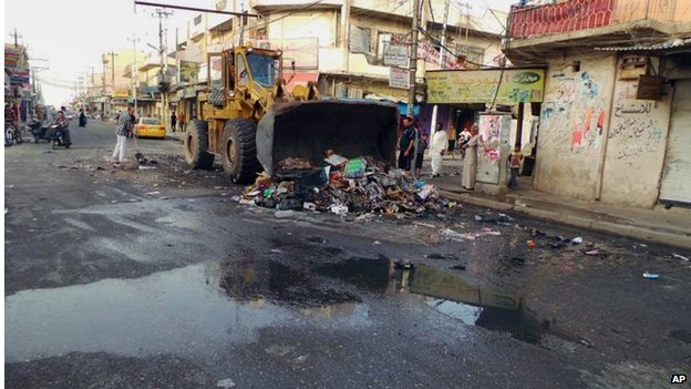 A municipality bulldozer and people clean a street in the northern city of Mosul (13 June 2014)