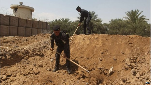 Iraqi policemen dig trenches at checkpoint in the Iraqi town of Taji, at the entrance of Baghdad (13 June 2014)