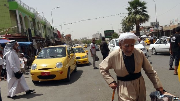 Iraqis walk on a street in the northern city of Kirkuk on 13 June 2014