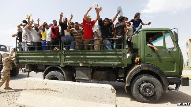 Volunteers who have joined the Iraqi Army to fight against the predominantly Sunni militants, who have taken over Mosul and other Northern provinces, gesture from an army truck in Baghdad 13 June 2014