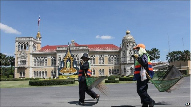 City workers carrying brooms and baskets inside the Government House compound on 31 May.