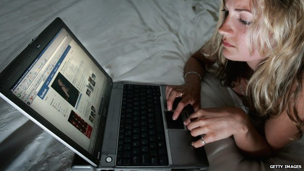 A woman browses Facebook on her laptop.