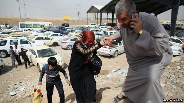 Families arrive at a checkpoint next to a temporary displacement camp in Kalak, Iraq  13 June 2014