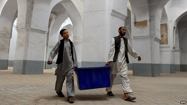 Afghan election workers move plastic boxes containing election material into a polling station at Jamee mosque in the city of Herat (13 June 2014)