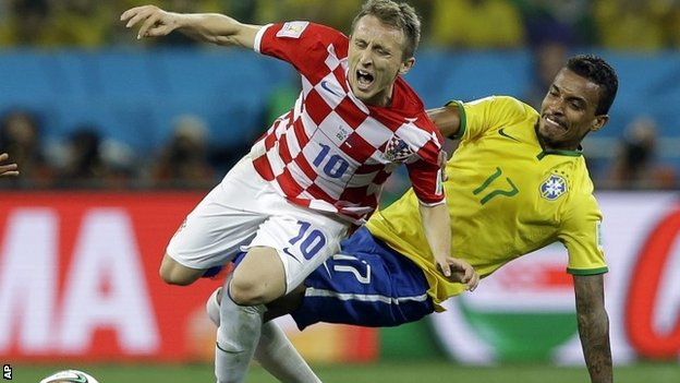 Luca Modric is tackled by Brazil's Luiz Gustavo