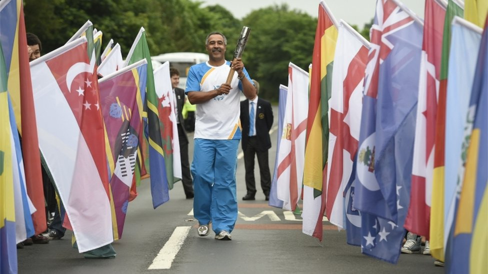 Daley Thompson carrying the Glasgow 2014 Queen's Baton across the bridge at Coldstream from England towards Scotland.