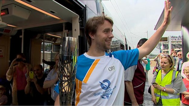 Scottish hockey player Allan Dick boards a tram with the baton at Murrayfield stadium
