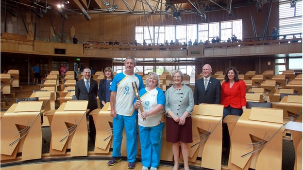 Gavin Hastings and batonbearer Lynne McNicoll with presiding officer Tricia Marwick in the Scottish Parlaiment chamber