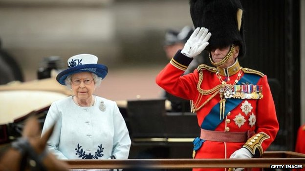 Queen and Duke of Edinburgh watch troops march past Buckingham Palace at Trooping the Colour on 14 June 2014