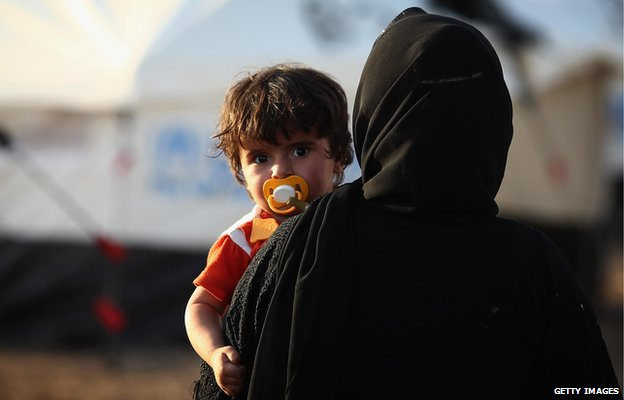 Woman holds child at displaced persons' camp, Kalak, Iraq (14 June)