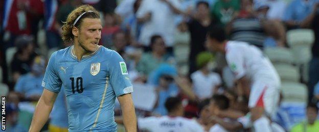 Diego Forlan looks pensive as Costa Rica celebrate scoring