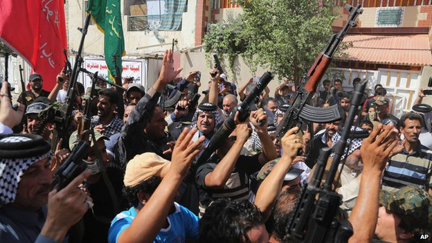 Iraqi Shiite tribal fighters raise their weapons in Baghdad's Sadr City,