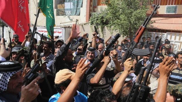 Iraqi Shia fighters raise their weapons and chant slogans in Baghdad's Sadr City, June 14, 2014