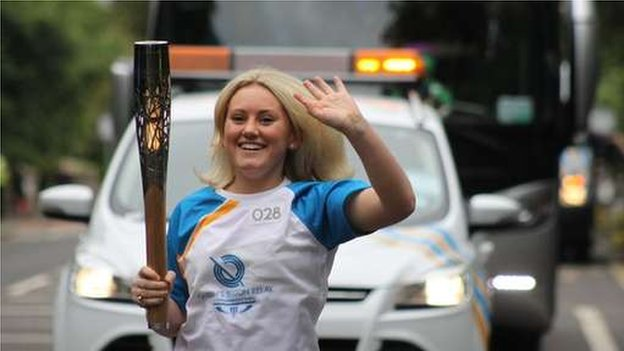 Beaming smile from Kirsten Alex Mills as she runs with the baton.