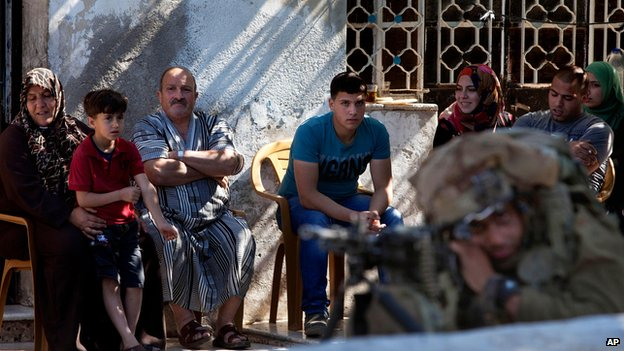 Palestinian family watches Israeli soldiers searching for missing teenagers, near Hebron (15 June)
