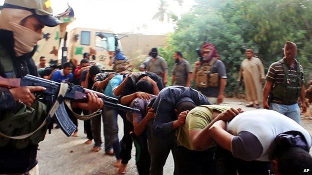 Picture apparently showing captured Iraqi soldiers in civilian clothes being led away by ISIS militants