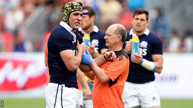 Scotland forward Kelly Brown is treated by team doctor
