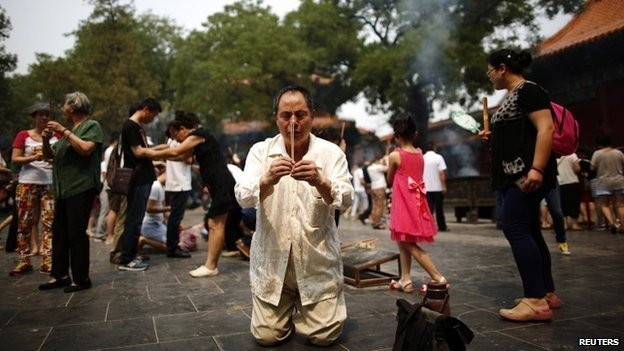 A family member of a passenger aboard the missing Malaysia Airlines flight MH370 burns incense as he prays at Yonghegong Lama Temple in Beijing June 15