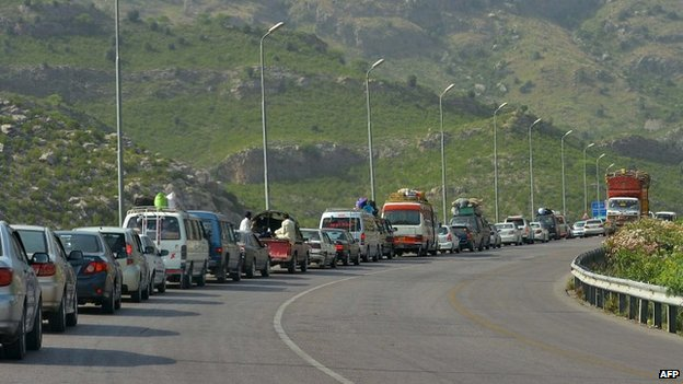 Civilians fleeing North Waziristan wait in a line of traffic to clear a check post near Darra Adam Khel on June 16, 2014.
