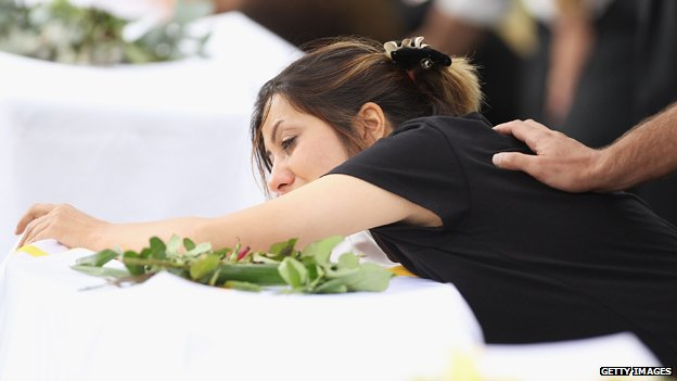 A mourner cries at the grave side at a Christian funeral service for the victims of the Christmas Island asylum seeker boat wreck at Castlebrook Memorial Park on February 15, 2011