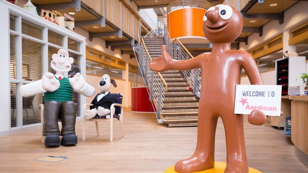 Wallace and Gromit and Morph together in what looks like a reception area (but is obviously . Morph is holding a sign saying 'Welcome to Aardman'