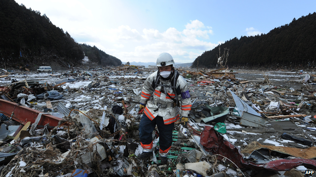 A Red Cross rescue worker walks through debris in March 2011