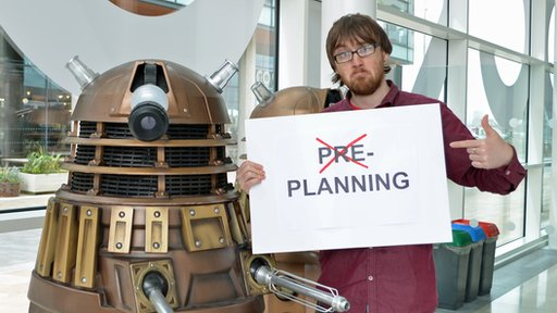 A dalek looks on as Colin Warhurst holds up a sign saying pre-planning and the pre is crossed out
