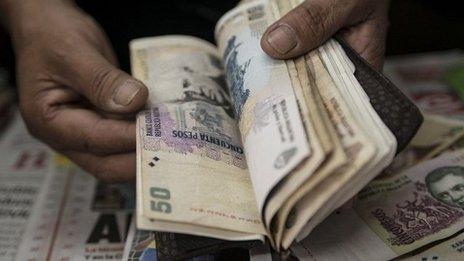 man counts Argentine pesos