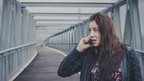 Young woman on phone on a bridge