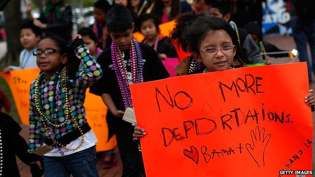 A child holds a sign protesting immigrant deportations at a demonstration outside the White House on 23 April, 2014.
