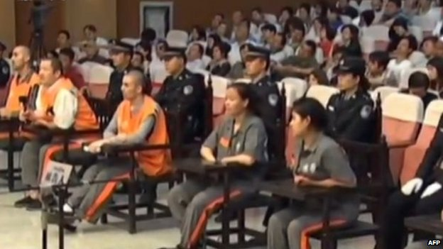 This screen grab taken from state broadcaster China Central Television (CCTV) footage on 16 June 2014 shows six of the eight prisoners (seated - in orange and brown) standing at the Intermediate People's Court in the Xinjiang capital Urumqi for the trial of those accused in the attack in October 2013 in Beijing's Tiananmen Square that killed two tourists