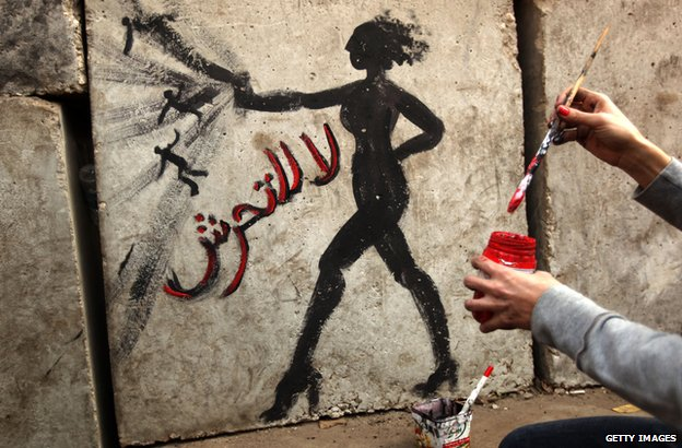 Graffiti showing a woman and reading in Arabic: 'No to Sexual Harassment' on a wall outside the presidential palace in Cairo