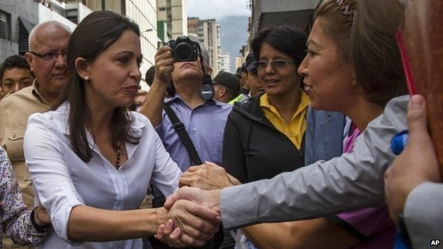Maria Machado shakes hand with supporter in Caracas