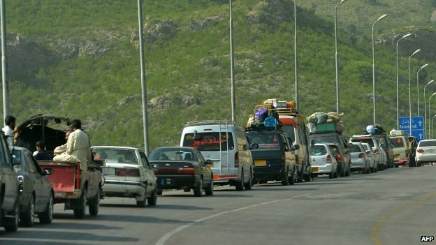 Civilians fleeing North Waziristan wait in a line of traffic to clear a check point near Darra Adam Khel on 16 June 2014