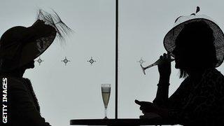 Racegoers enjoy a glass of champagne at Royal Ascot