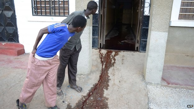 Men look at a pool of blood at the entrance of a restaurant in Mpeketoni. Photo: 16 June 2014