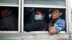 Cambodian workers look out of a bus window after crossing the Thai border
