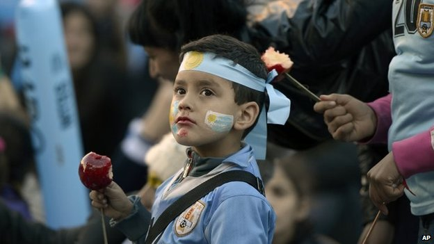 A fan of Uruguay's national soccer team eats a toffee apple as he watches the Brazil 2014 World Cup match between Costa Rica and Uruguay on 14 June, 2014