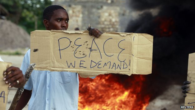 A resident holds a placard at a protest against the recent attack in the coastal Kenyan town of Mpeketoni on 17 June 2014.