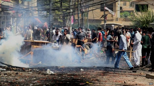 Supporters of an anti-Taliban cleric hurl stones toward policemen during clashes in Lahore, Pakistan, 17 June  2014