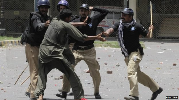 Policemen beat and detain a supporter of Muhammad Tahirul Qadri, Sufi cleric and leader of political party Pakistan Awami Tehreek, during a protest in Lahore, 17 June 2014