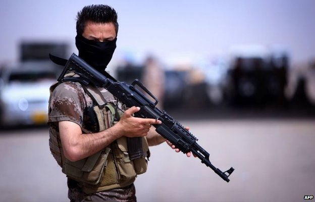 Iraqi Kurdish Peshmerga fighter at a camp set up for those fleeing the violence in Nineveh province (13 June 2014)