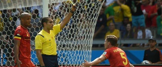 Belgium defender Jan Vertonghen is shown a yellow card after fouling Sofiane Feghouli