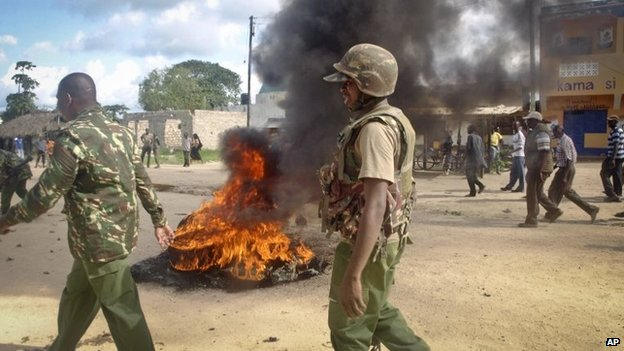 "Armed security forces walk past a barricade of burning tyres set up by residents to protest against the recent killings and what they claimed was the government""s failure to provide them with enough security, in the village of Kibaoni just outside the town of Mpeketoni, about 60 miles (100 kilometers) from the Somali border on the coast of Kenya Tuesday, June 17, 2014."