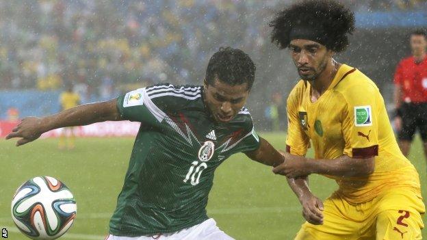Benoit Assou-Ekotto of Cameroon challenges Mexico's Giovani dos Santos.
