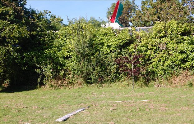 Plane in field off Forest Road, Guernsey, with debris in the garden of a property