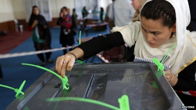 An Afghan election worker checks a seal on a ballot box after voting closed at a polling station in Kabul 14 June 2014.