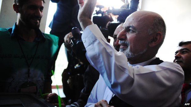 Afghan presidential candidate Ashraf Ghani gestures as he casts his vote at a polling station in Kabul on 14 June 2014.