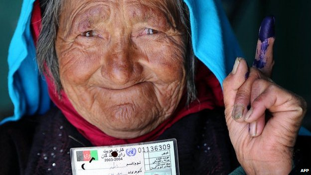 An Afghan resident holds her voter card after casting her ballot at a polling station in Bamiyan province on 14 June 2014.